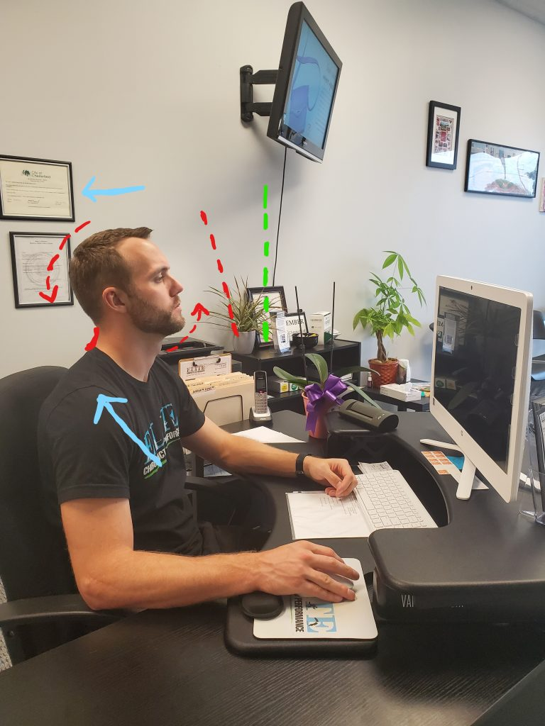 Showing an extended neck position at a computer.