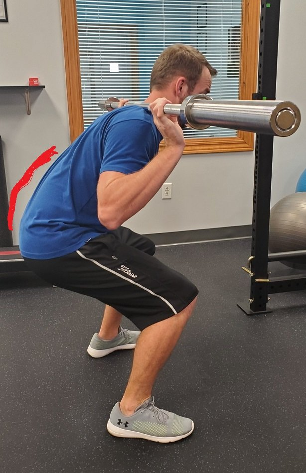 Rounding the back during a squat.
