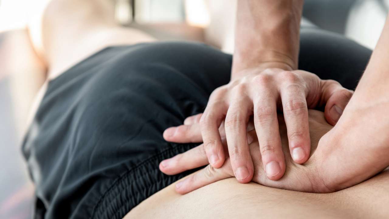 A chiropractor putting hands on the lower back.