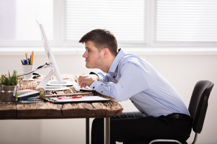 A man sitting with bad posture at the computer.