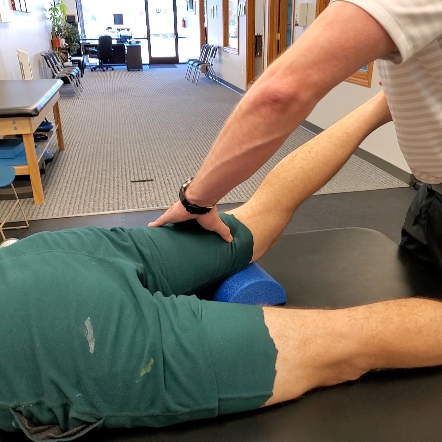 A Dr. using myofascial release on the hamstrings.