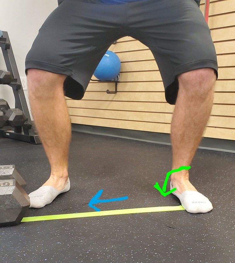 Using a band to stabilize the foot during a squat.