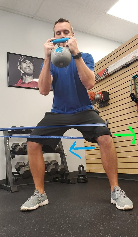 Using a band to prevent inward knee during squat.