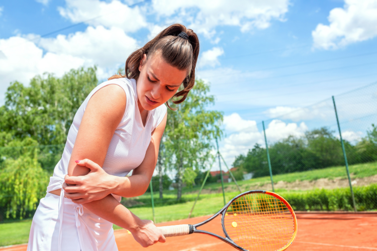 A tennis player holding their elbow in pain.