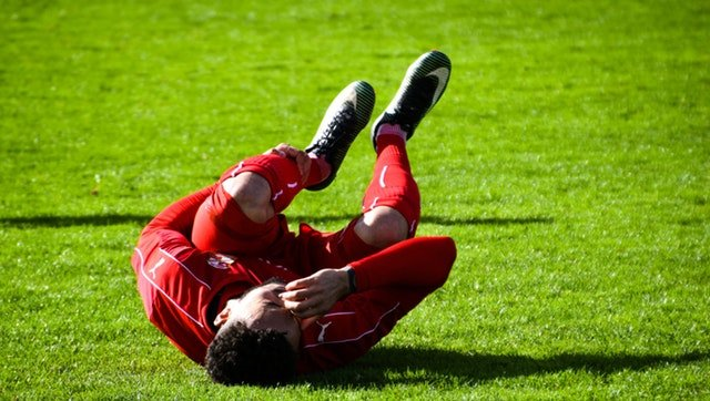 Soccer player injured on the ground.